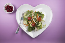 Traditional Salad On A Heart Shaped Plate With A Bowl Of Pomegranate On A Pink Background