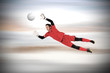 Fit goal keeper jumping up against grey blurred background