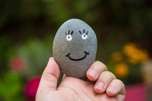 Hand Holding A Round Stone With A Happy Face Painted On It