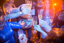 High Angle View At Multi-ethnic Group Of Laughing Young People Enjoying Dance Party In Nightclub And Drinking Champagne, Focus On Clinking Glasses
