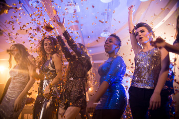 Multi-ethnic group  of beautiful young women wearing glittering dresses dancing under golden confetti shower enjoying raving party in nightclub