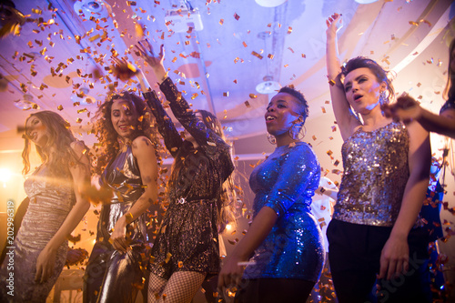 Multi-ethnic group  of beautiful young women wearing glittering dresses dancing under golden confetti shower enjoying raving party in nightclub