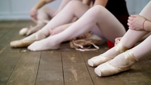 Close Up, Ballerinas Change Their Shoes Into Special Ballet Shoes, Pointe Shoes, Lace With Ballet Ribbons, On An Old Wooden Floor, In Ballet Class.