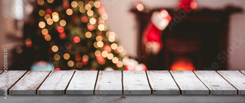 Wooden desk against close up of christmas lights Canvas Print
