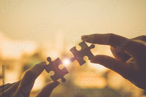 Photographie  Silhouette Woman hands connecting couple puzzle piece against sunrise effect, businesswoman holding jigsaw with sunset background