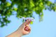 Samolot zabawka w dłoni dziewczyny na tle błękitnego nieba i zielonych liści.