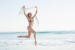 Gleeful slender woman jumping in the air holding shawl