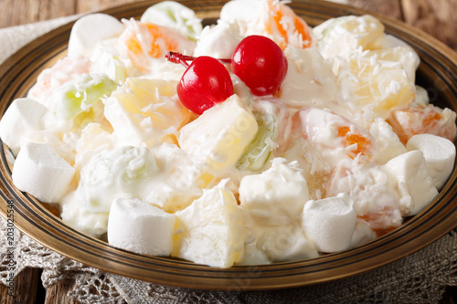 Photo Dessert fruit salad Ambrosia from pineapple, tangerine, grapes and marshmelou with vanilla yogurt close-up