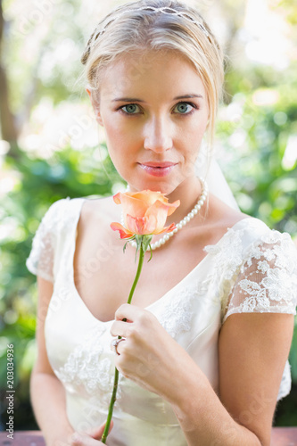 21f60ea551994 Smiling blonde bride in pearl necklace holding rose - Buy this stock ...