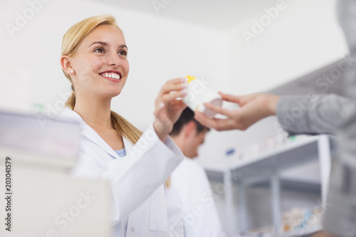 Photo  Pharmacist giving a drug box to a patient