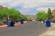 Blue Trash Cans Line The Stree...