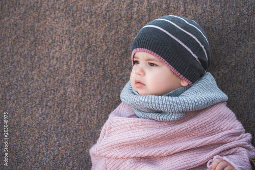 236f8063bc38 Cute baby girl wearing a warm winter hat and a colorful scarf on a ...
