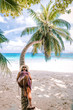 young woman with hat at the beach with palm tree Seychelles white tropical island