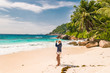 young woman at the beach during vacation at the tropical islands of the Seychelles with huge granite rocks