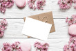 blank greeting card or wedding invitation in frame made of pink cherry blossoming or sakura over white wooden table