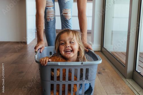 Fotografie, Obraz  Little girl and her mother having fun doing laundry