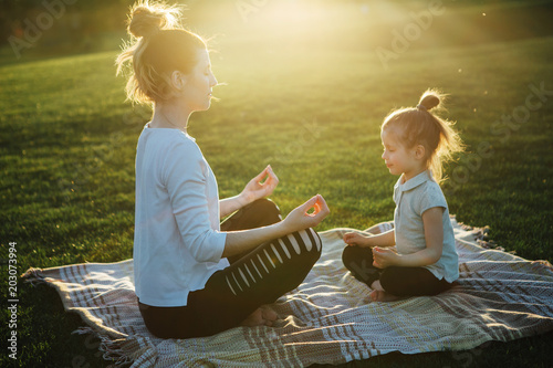 Fotografía  Mother practicing yoga with her daughter in the open air.