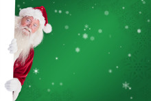 Santa Looks Out Behind A Wall Against Green Snowflake Background