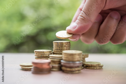 Photographie Saving money concept . hand putting money coin stack