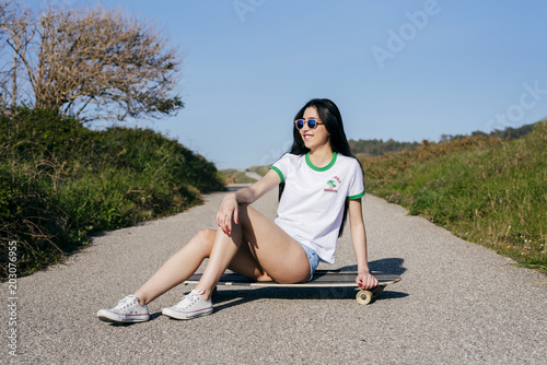 Teen girl on long board in nature