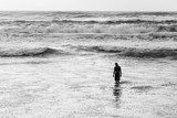 Silhouette of a man standing knee deep in ocean waves in black and white - 203082383
