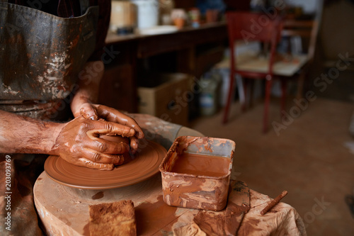Aluminium Prints Old abandoned buildings Close-up hands of a male potter in apron molds bowl from clay, selective focus