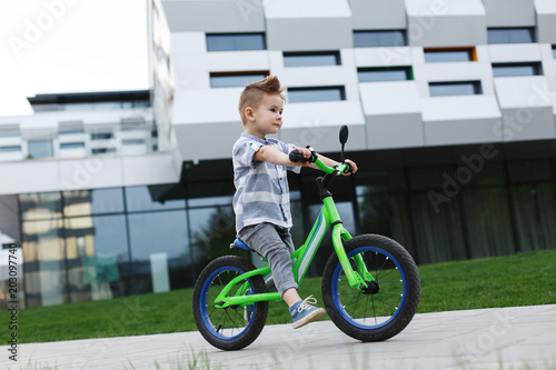 Photo  Happy little boy rides bicycle on the road in park