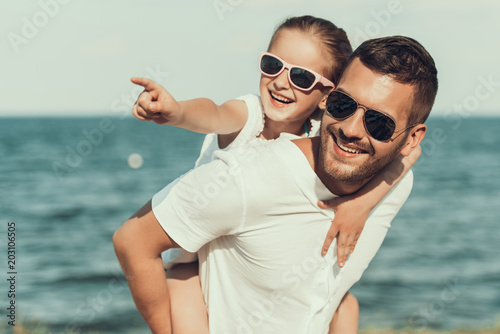 Happy little daughter in sunglasses sits on fathers back.