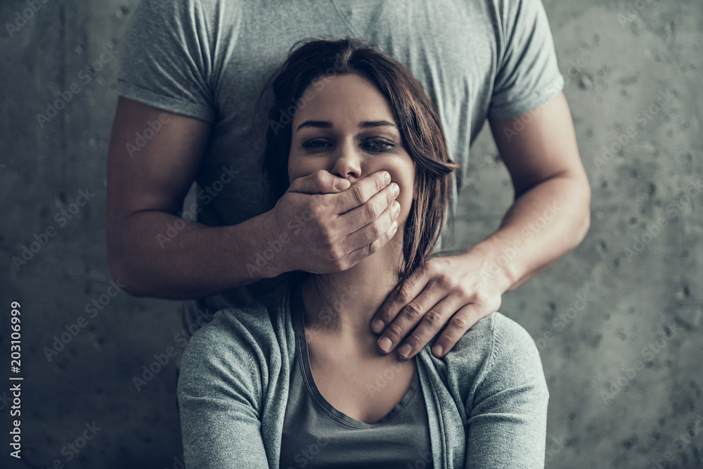 Fototapeta Man closes by hand mouth of oppressed woman.