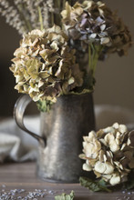 Close-up Of Dry Hydrangea And Lavender In Vase On Wooden Table