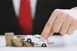 Business man in suit and red necktie holding model of toy car on over a lot of stacked coins - insurance, loan and buying car concept