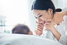 Mother's Hands Holding Newborn Baby Feet. Close Up Portrait Of Beautiful Young Asian Mother With Her Newborn Baby. Healthcare And Medical Love Lifestyle Mother's Day Concept