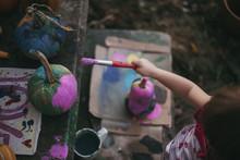 High Angle View Of Girl Painting Pumpkin At Backyard During Halloween
