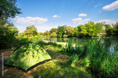 Fotobehang Pistache Green tent on the river bank