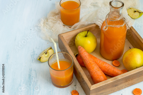 Carrot juice in a glass bottle and in a glass, next to a fresh carrot and apples on an old wooden table. The source of natural vitamins and minerals.