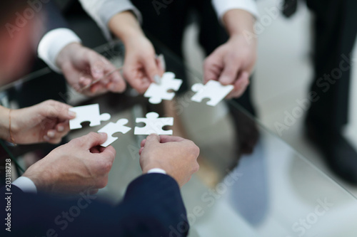 Business people holding jigsaw puzzle. Canvas Print