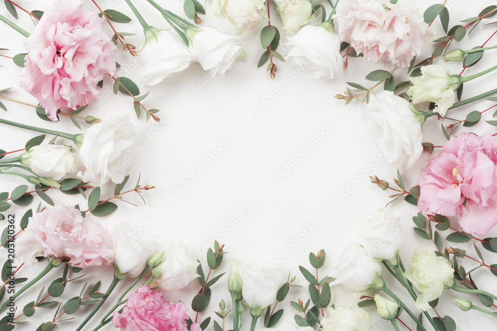 Fototapeta Beautiful floral frame of pastel flowers and eucalyptus leaves on white table top view. Flat lay style.