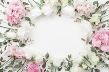 Beautiful floral frame of pastel flowers and eucalyptus leaves on white table top view. Flat lay style.