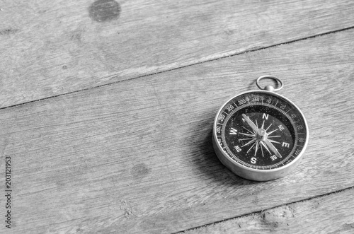 Old compass on wooden table.