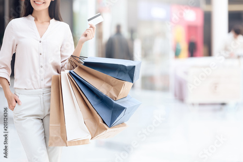Fotografía  Happy brunette with shopping bags at mall. Sale.