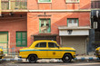 An Ambassador yellow cab taxi is parked in the street under a red-colored house in Kolcata, India