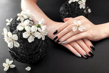 Black And Silver Manicure With Cherry Blossom On Black Background. Woman With Black Nails Surrounded With White Flowers