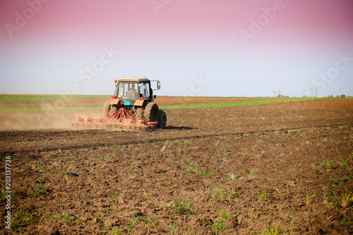 Poster de jardin Desert de sable Tractor fertilize field before seeding