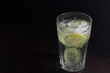 Cold drink with ice, cucumber and lime on dark low key background