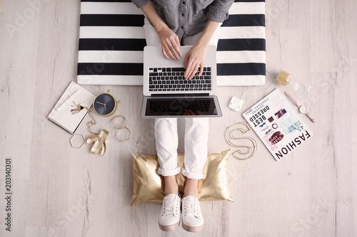 Female blogger with laptop indoors, top view