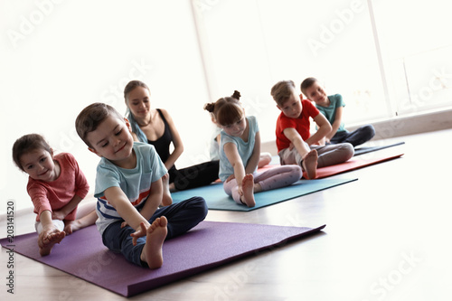 Foto op Aluminium Ontspanning Little children and their teacher practicing yoga in gym