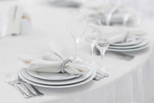 Silver Cutlery And Stylish White Plates Are Laid Out On A White Tablecloth Of Expensive Fabric In A Restaurant For A Festive Banquet