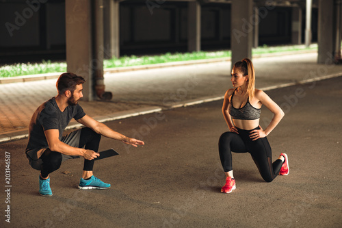 Young woman exercising with personal trainer
