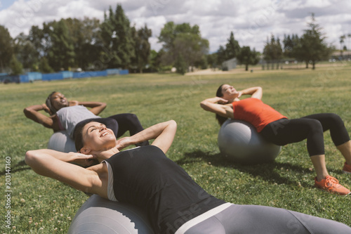 Smiling woman with friends exercising on ball at park during sunny day