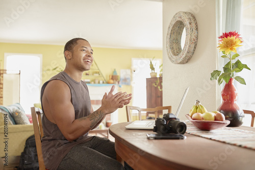 Happy young man with laptop clapping while sitting at table in house